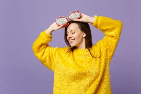 Relaxed young woman in fur sweater keeping eyes closed holding halfs of pitahaya, dragon fruit isolated on violet pastel background. People vivid lifestyle relax vacation concept. Mock up copy space Imagens