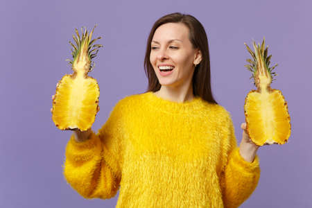 Cheerful young woman in fur sweater looking aside holding halfs of fresh ripe pineapple fruit isolated on violet pastel background. People vivid lifestyle, relax vacation concept. Mock up copy space