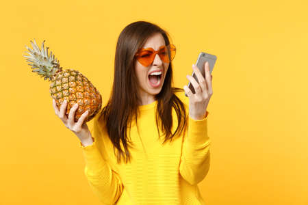 Screaming young woman in heart sunglasses holding ripe pineapple fruit talking on mobile phone isolated on yellow orange background. People vivid lifestyle, relax vacation concept. Mock up copy space