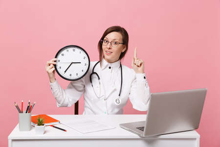Female doctor sit at desk work on computer with medical document hold clock in hospital isolated on pastel pink wall background. Woman in medical gown glasses stethoscope. Healthcare medicine concept Banque d'images - 120967023