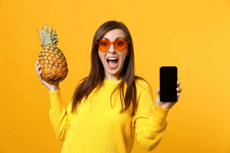 Surprised young woman in sunglasses hold pineapple fruit, mobile phone with blank empty screen isolated on yellow orange background. People vivid lifestyle, relax vacation concept. Mock up copy space