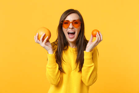 Funny screaming young woman in heart glasses hold in hands fresh ripe mandarin orange fruit isolated on yellow background in studio. People vivid lifestyle, relax vacation concept. Mock up copy space