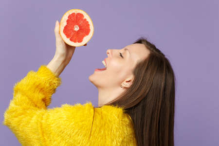 Side view of cheerful young woman in fur sweater holding in hand half of fresh ripe grapefruit isolated on violet pastel background. People vivid lifestyle, relax vacation concept. Mock up copy space Imagens