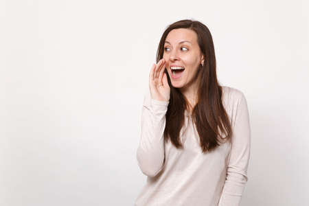 Cheerful young woman in light clothes looking aside, whispers gossip, tells secret with hand gesture isolated on white wall background. People sincere emotions, lifestyle concept. Mock up copy space
