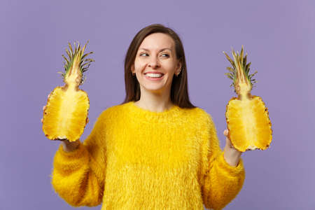 Smiling young woman in fur sweater looking aside holding halfs of fresh ripe pineapple fruit isolated on violet pastel background. People vivid lifestyle, relax vacation concept. Mock up copy space