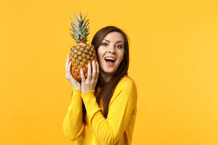 Excited young woman in casual clothes keeping mouth open, holding fresh ripe pineapple fruit isolated onyellow orange background. Peoplevivid lifestyle, relax vacation concept. Mock up copy space