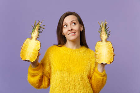 Pensive cute young woman in fur sweater looking up holding halfs of fresh ripe pineapple fruit isolated on violet pastel background. People vivid lifestyle, relax vacation concept. Mock up copy space