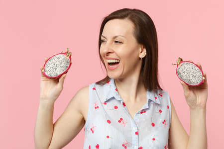 Cheerful young woman looking aside, holding halfs of fresh ripe pitahaya, dragon fruit isolated on pink pastel background in studio. People vivid lifestyle relax vacation concept. Mock up copy space