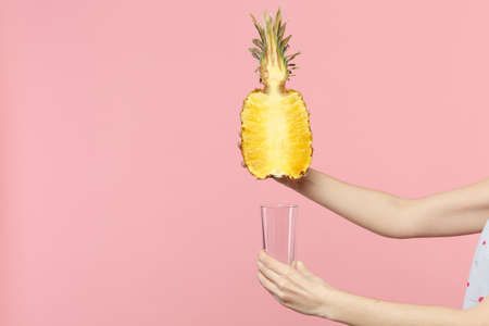 Close up cropped photo of female hold in hands half of fresh ripe pineapple fruit, glass cup isolated on pink pastel wall background. People vivid lifestyle relax vacation concept. Mock up copy space