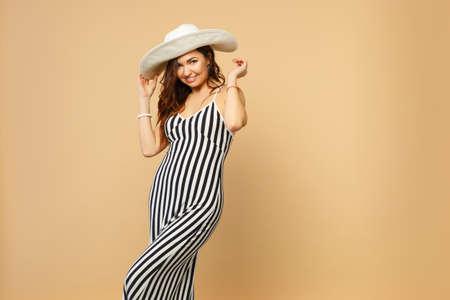 Porträt einer schönen Frau in schwarz-weiß gestreiftem Kleid, Hut stehend, Kamera isoliert auf pastellbeigem Hintergrund im Studio suchen. Menschen aufrichtige Emotionen Lifestyle-Konzept. Mock-up-Kopierraum
