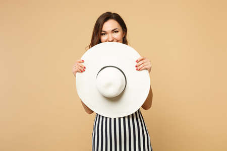 Portrait of cute young woman in black and white striped dress covering face with hat isolated on pastel beige wall background in studio. People sincere emotions, lifestyle concept. Mock up copy space Фото со стока