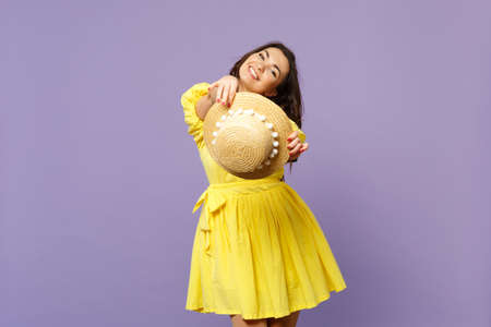 Portrait of pretty stunning young woman in yellow dress holding summer hat looking camera isolated on pastel violet background in studio. People sincere emotions lifestyle concept. Mock up copy space