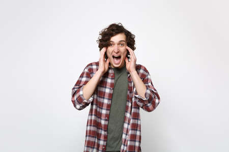 Portrait of crazy screaming young man in casual clothes looking camera, keeping hands near face isolated on white background in studio. People sincere emotions, lifestyle concept. Mock up copy space Imagens