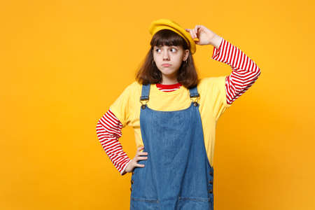 Portrait of preoccupied girl teenager in french beret, denim sundress putting hand on head, looking aside isolated on yellow background. People sincere emotions, lifestyle concept. Mock up copy space