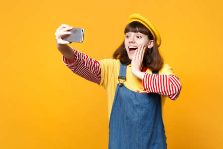 Excited girl teenager in french beret, denim sundress doing selfie shot on mobile phone, putting hand on cheek isolated on yellow background. People emotions, lifestyle concept. Mock up copy space Stock Photo