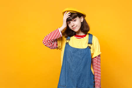 Portrait of bright girl teenager in french beret and denim sundress putting hand on head isolated on yellow wall background in studio. People sincere emotions, lifestyle concept. Mock up copy space