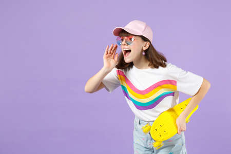 Cheerful teen girl in vivid clothes, eyeglasses hold skateboard, looking aside screaming with hand gesture isolated on violet background. People sincere emotions lifestyle concept. Mock up copy space Imagens