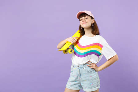 Portrait of pretty teen girl in vivid clothes looking camera, holding yellow skateboard isolated on violet pastel background in studio. People sincere emotions, lifestyle concept. Mock up copy space 版權商用圖片