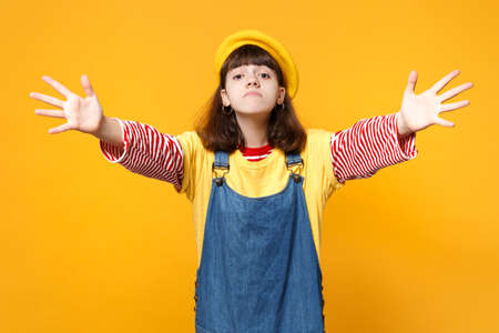 Upset girl teenager in french beret, denim sundress spreading outstretched hands, pointing on camera isolated on yellow wall background. People sincere emotions, lifestyle concept. Mock up copy space Stock Photo
