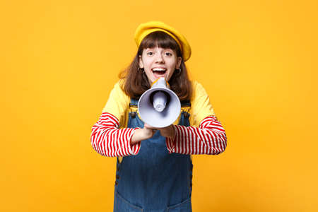 Portrait of joyful pretty girl teenager in french beret, denim sundress scream in megaphone isolated on yellow wall background in studio. People sincere emotions lifestyle concept. Mock up copy space