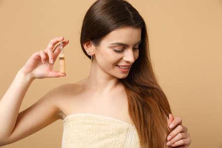 Nahaufnahme brünette halbe Frau 20er Jahre mit perfekter Haut, Make-up einzeln auf beige pastellfarbenem Wandhintergrund, Studioporträt. Konzept für kosmetische Verfahren der Hautpflege im Gesundheitswesen. Mock-up-Kopierraum Standard-Bild