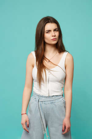 Portrait of perplexed bewildered young woman in light casual clothes looking camera isolated on blue turquoise background in studio. People sincere emotions, lifestyle concept. Mock up copy space 写真素材