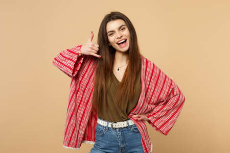 Portrait of cheerful young woman in casual clothes doing phone gesture like says call me back isolated on pastel beige wall background. People sincere emotions, lifestyle concept. Mock up copy space