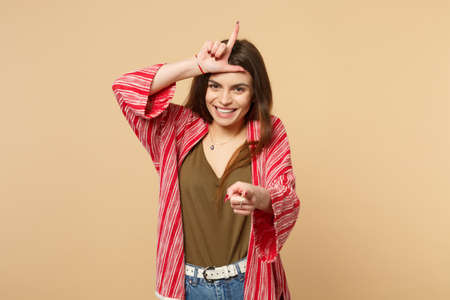 Laughing young woman in casual clothes showing loser gesture, pointing index finger on camera isolated on pastel beige wall background. People sincere emotions, lifestyle concept. Mock up copy space