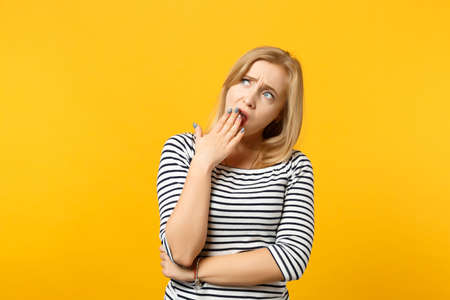 Portrait of tired young woman in striped clothes looking aside up, yawning covering mouth with hand isolated on yellow orange background. People sincere emotions lifestyle concept. Mock up copy space