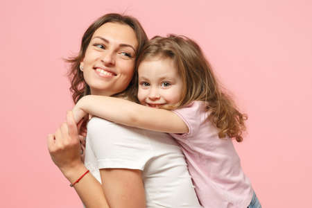 Woman in light clothes have fun with cute child baby girl. Mother, little kid daughter isolated on pastel pink wall background, studio portrait. Mother's Day love family, parenthood childhood concept Banque d'images