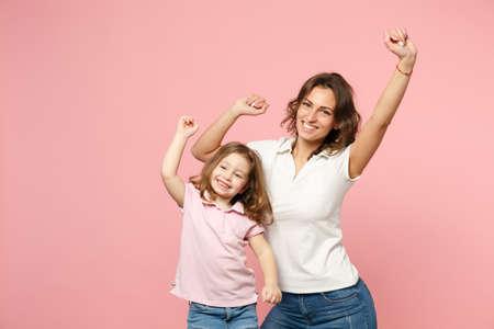 Une femme en vêtements légers s'amuse avec une jolie petite fille. Mère, petite fille isolée sur fond de mur rose pastel, portrait en studio. Famille d'amour de la fête des mères, concept d'enfance de la parentalité
