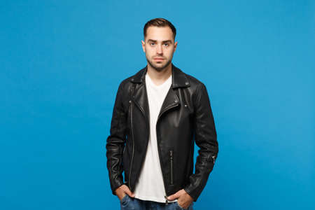 Handsome stylish young bearded man in black leather jacket white t-shirt looking camera isolated on blue wall background studio portrait. People sincere emotions lifestyle concept. Mock up copy space 免版税图像