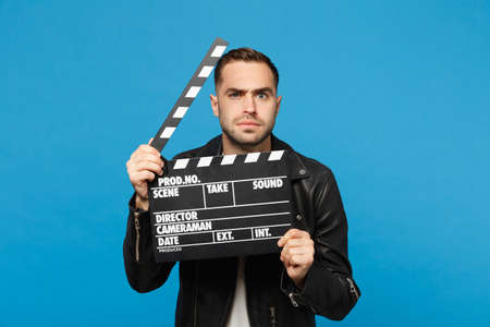 Handsome stylish young unshaven man in black jacket white t-shirt hold in hand film making clapperboard isolated on blue wall background studio portrait. People lifestyle concept. Mock up copy space