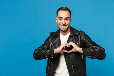 Handsome stylish young unshaven man in black leather jacket white t-shirt looking camera isolated on blue background studio portrait. People sincere emotions lifestyle concept. Mock up copy space 写真素材