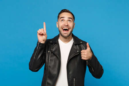 Stylish young bearded man in black leather jacket white t-shirt holding index finger up with great new idea isolated on blue background. People sincere emotions lifestyle concept. Mock up copy space