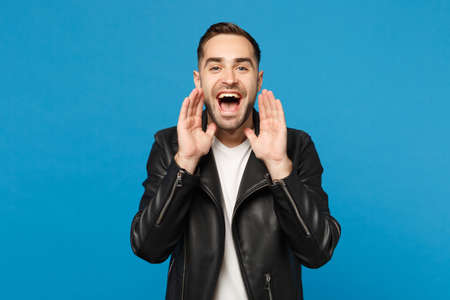 Stylish young bearded man in black leather jacket white t-shirt screaming, hand at mouth isolated on blue background studio portrait. People sincere emotions lifestyle concept. Mock up copy space