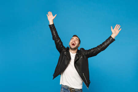 Stylish young happy bearded man in black leather jacket white t-shirt doing winner gesture say Yes isolated on blue background studio portrait. People sincere emotions concept. Mock up copy space Reklamní fotografie