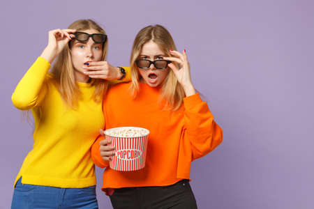 Two bewildered young blonde twins sisters girls in 3d imax glasses watching movie film hold popcorn isolated on pastel violet blue wall background. People family lifestyle concept. Mock up copy space