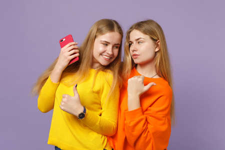 Two young blonde twins sisters girls in vivid clothes pointing thumb aside, holding mobile phone isolated on pastel violet blue wall background. People family lifestyle concept. Mock up copy space