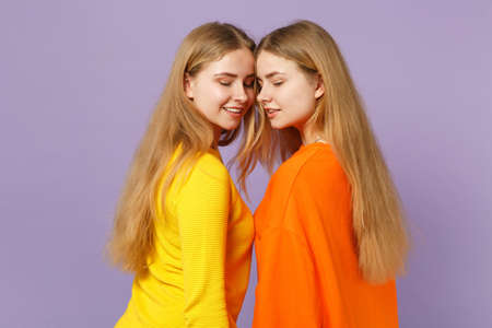 Side view of two pretty blonde twins sisters girls in vivid colorful clothes looking down isolated on pastel violet blue wall background in studio. People family lifestyle concept. Mock up copy space