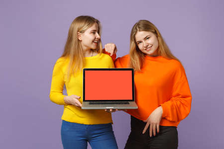 Two smiling young blonde twins sisters girls in vivid clothes hold laptop pc computer with blank empty screen isolated on violet blue background. People family lifestyle concept. Mock up copy space Banque d'images - 127896568