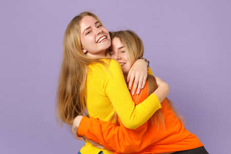 Two cheerful young blonde twins sisters girls in vivid colorful clothes hugging and looking camera isolated on pastel violet blue wall background. People family lifestyle concept. Mock up copy space
