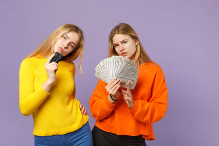 Two attractive blonde twins sisters girls holding credit bank card fan of money in dollar banknotes, cash money isolated on violet blue background. People family lifestyle concept. Mock up copy space