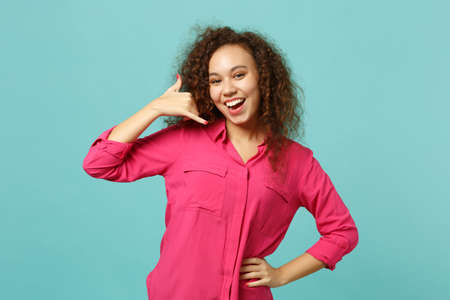 Portrait of joyful african girl in casual clothes doing phone gesture like says call me back isolated on blue turquoise wall background. People sincere emotions, lifestyle concept. Mock up copy space
