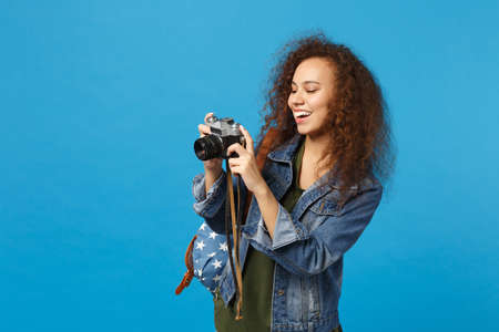 Young african american girl teen student in denim clothes backpack hold camera isolated on blue background studio portrait. Education in high school university college concept. Mock up copy space