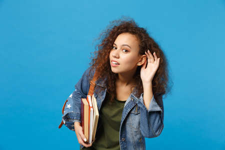 Young sad african american girl teen student in denim clothes, backpack hold books isolated on blue background studio portrait. Education in high school university college concept. Mock up copy space