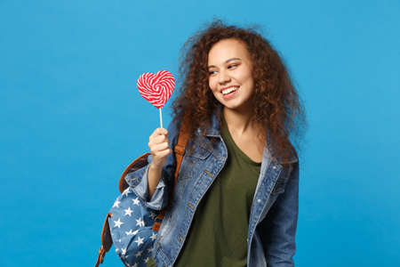 Young african american girl teen student in denim clothes, backpack hold candy isolated on blue background studio portrait. Education in high school university college concept. Mock up copy space