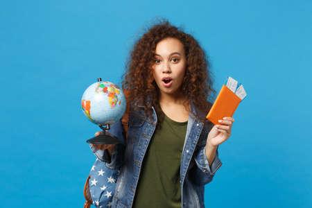 Jeune étudiante adolescente afro-américaine dans des vêtements en denim, sac à dos hold pass isolé sur fond de mur bleu portrait en studio. Éducation dans le concept de collège universitaire secondaire. Maquette de l'espace de copie Banque d'images