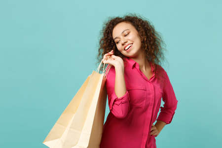 Joyful african girl in pink casual clothes holding package bag with purchases after shopping isolated on blue turquoise wall background. People sincere emotions lifestyle concept. Mock up copy space