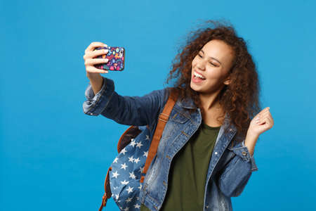 Young african american girl teen student in denim clothes, backpack hold phone isolated on blue background studio portrait. Education in high school university college concept. Mock up copy space